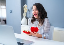 woman opening a heart-shaped box in front of her computer