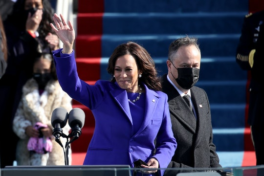 Kamala Harris waves to the Inauguration crowd, her husband Doug Emhoff behind her.