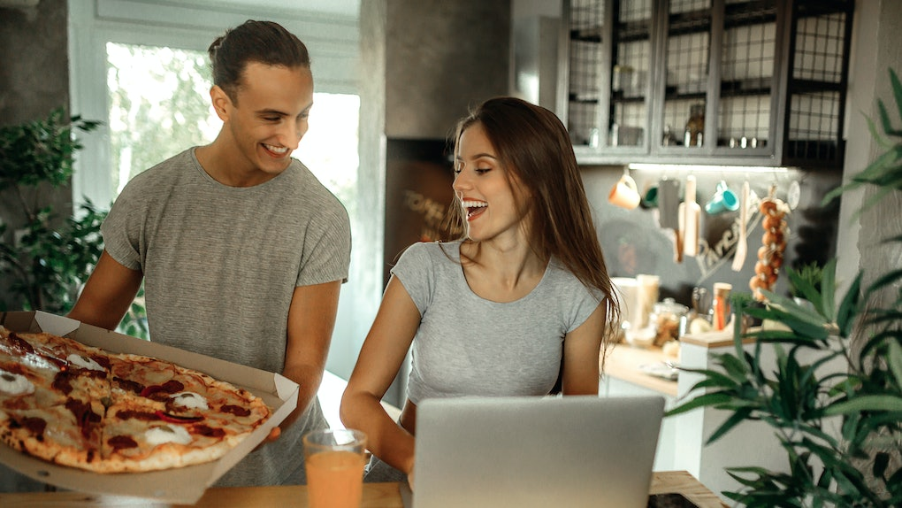 A happy couple looks at a pizza while setting up their laptop for a Zoom party in their kitchen.