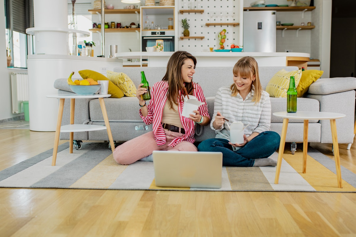 Two friends enjoy takeout on the floor while enjoying a virtual event on their laptop.