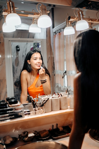 A single woman applies lipstick in her bathroom mirror on Valentine's Day.
