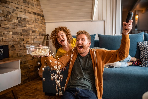 A young couple cheers in their home while eating popcorn and watching the Super Bowl.