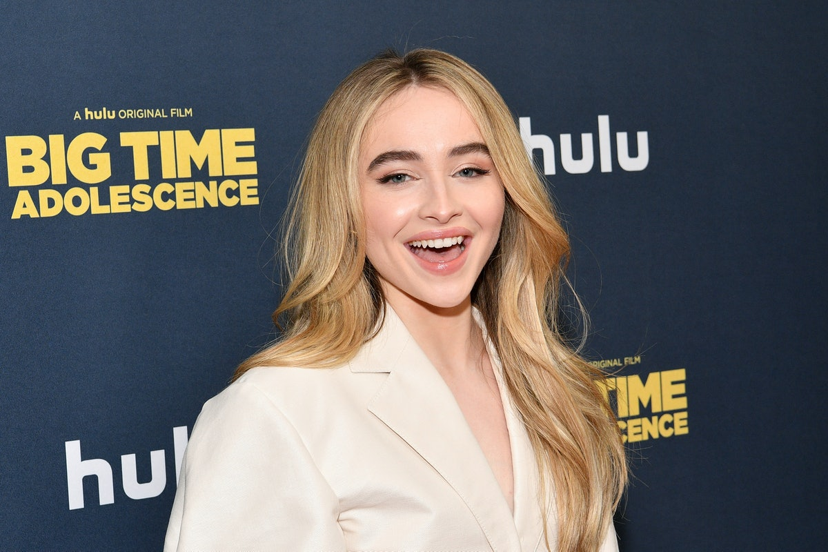 Sabrina Carpenter smiles on the red carpet in a white suit.