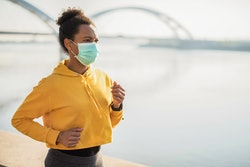 A woman in a yellow track jacket jogs with a mask on. How covid vaccines will affect your mental health.