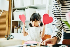 little girl with two valentine's heart cards