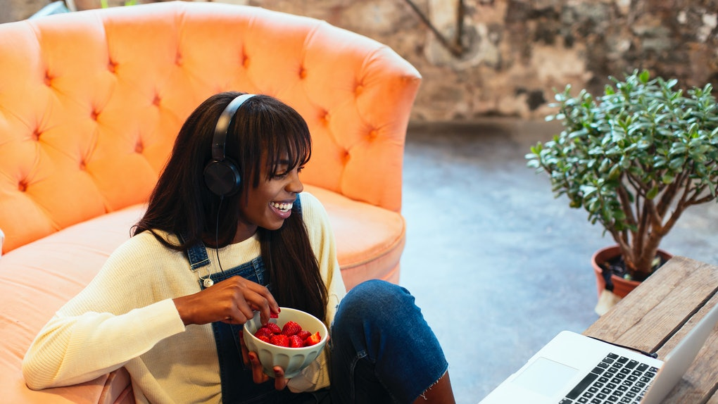 A young Black woman eats strawberries while video chatting and playing games with her friends on Galentine's Day.