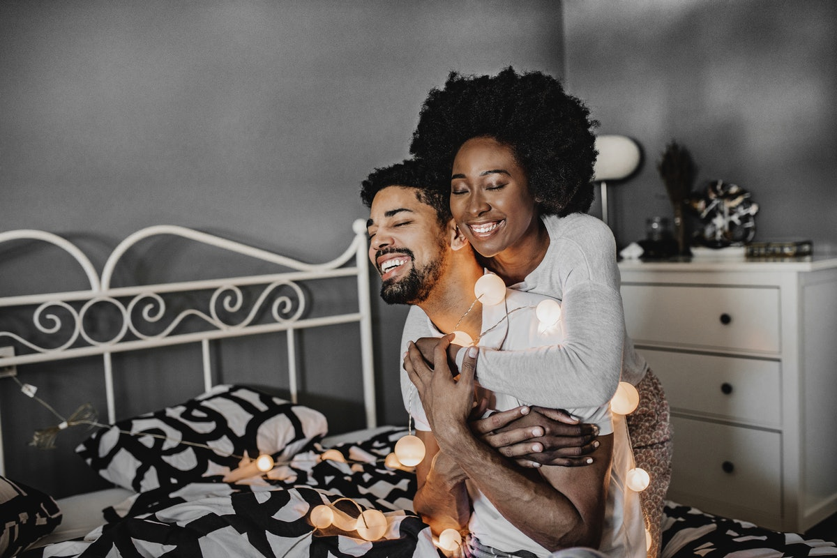 A happy couple embraces on a bed surrounded by fairy lights.