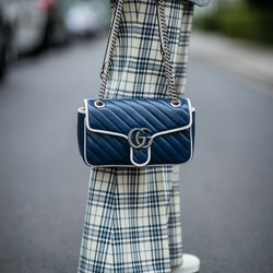 A person wearing plaid pants and holding a blue Gucci Marmont bag.