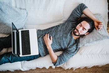 man sleeping on couch with laptop