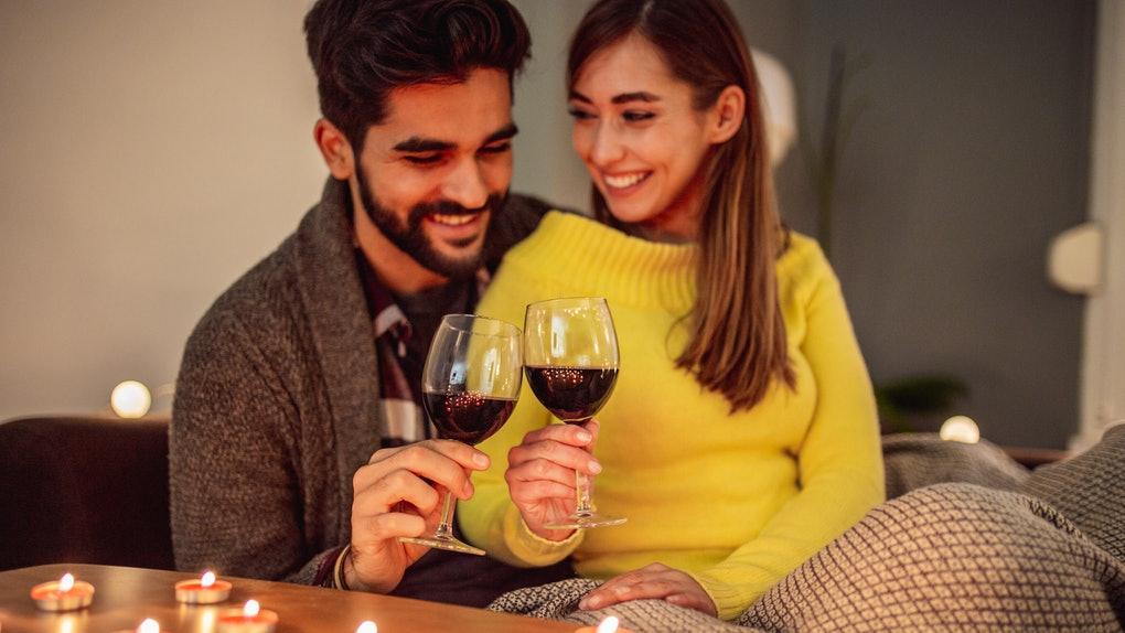 A happy couple snuggles on the couch and enjoys red wine during their at-home Valentine's Day date.