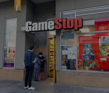 Two pedestrians can be seen outside a GameStop storefront.