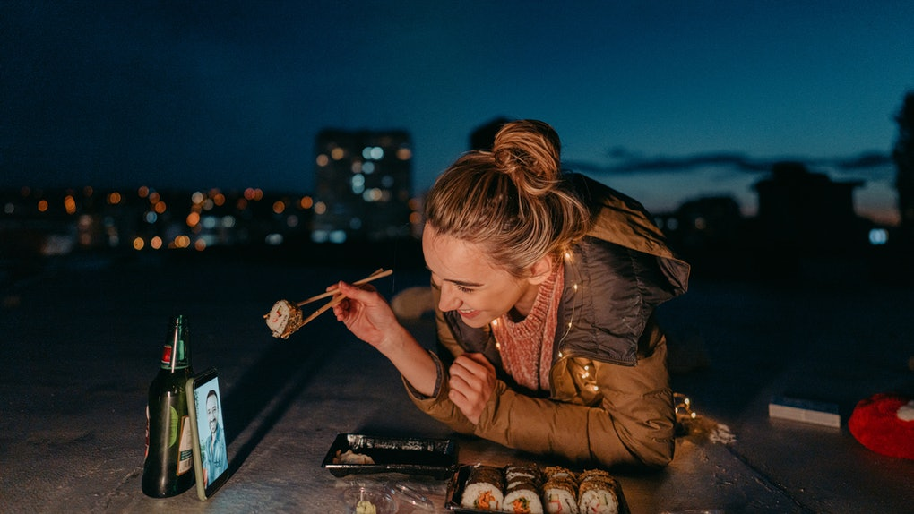 A happy woman smiles while enjoying sushi on a rooftop, on a virtual Valentine's Day date with her partner.