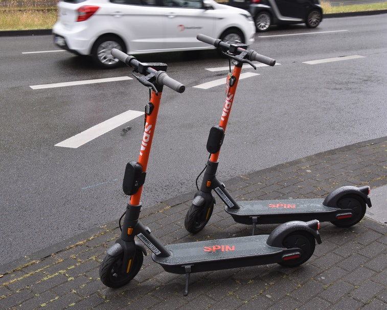 Two dockless electric scooters parked side by side on a sidewalk.