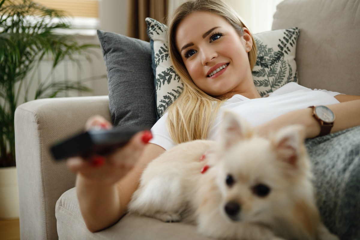 A young woman watches Puppy Bowl 2021 with her dog while sitting on the couch.