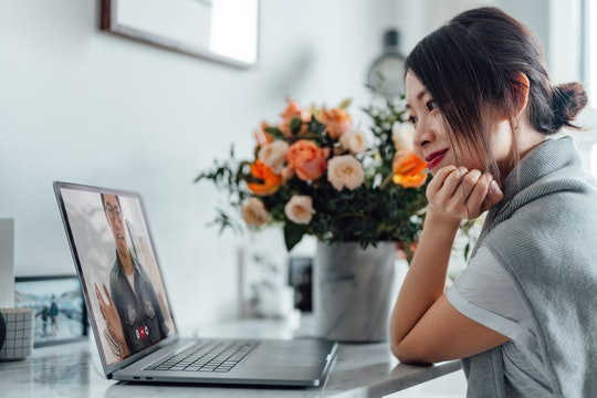 woman with flowers looking at laptop
