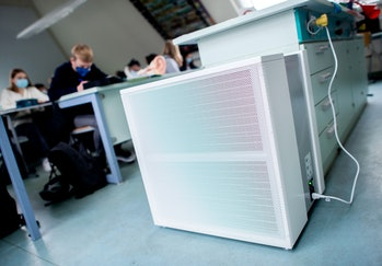air filters in an office with workers sitting at desks