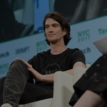 WeWork CEO Adam Neumann is seen at a panel. He is wearing a microphone and sitting on a couch.