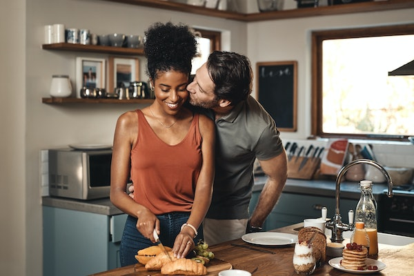 A happy woman cuts a croissant in a bright kitchen while her husband gives her a kiss.