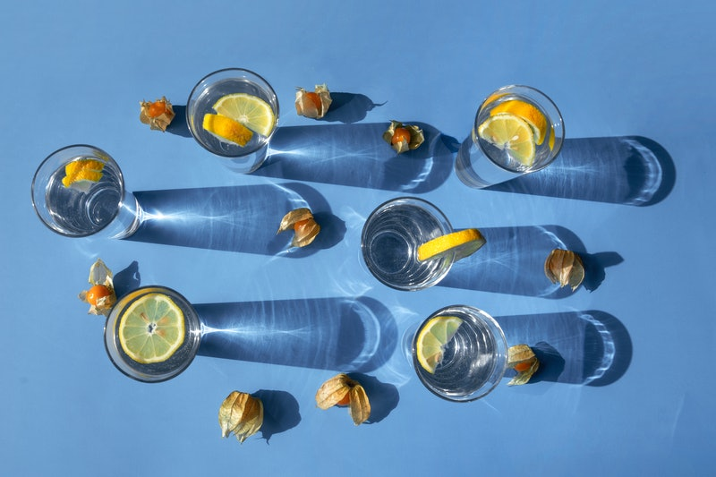 Glasses of seltzer with lemon on a blue background. Dry january delayed one woman's sobriety - here's how.