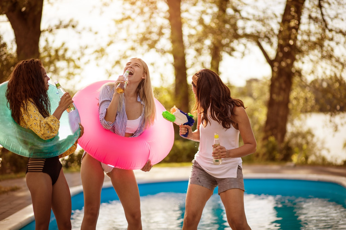 Three women laugh by the pool, chilling out with a floatie and some drinks.