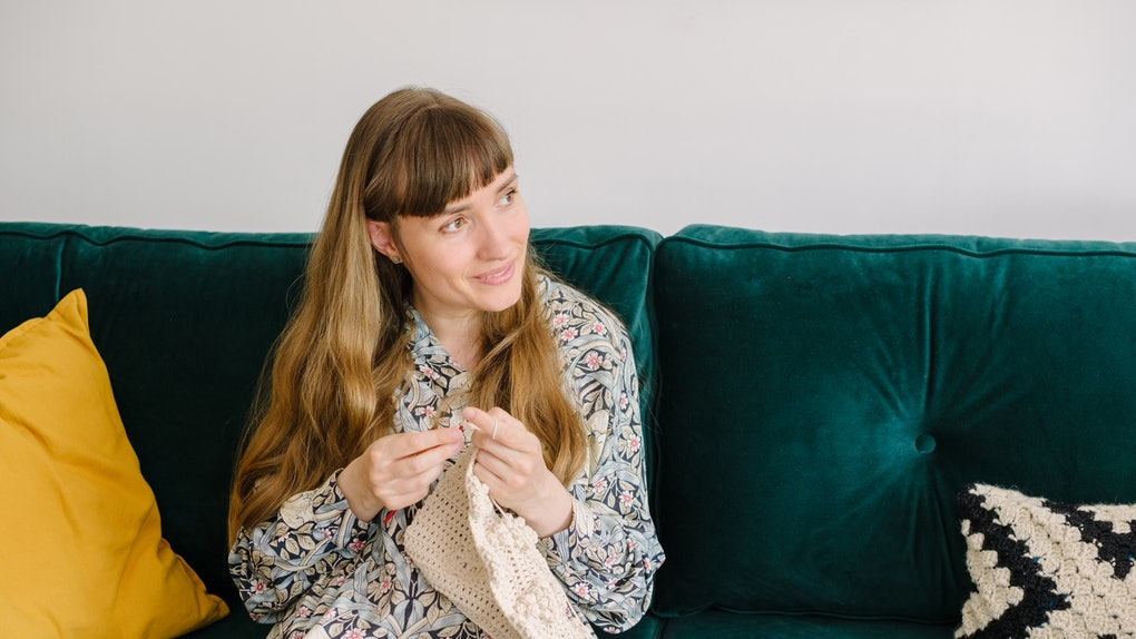A woman crochets a blanket while sitting on her couch.