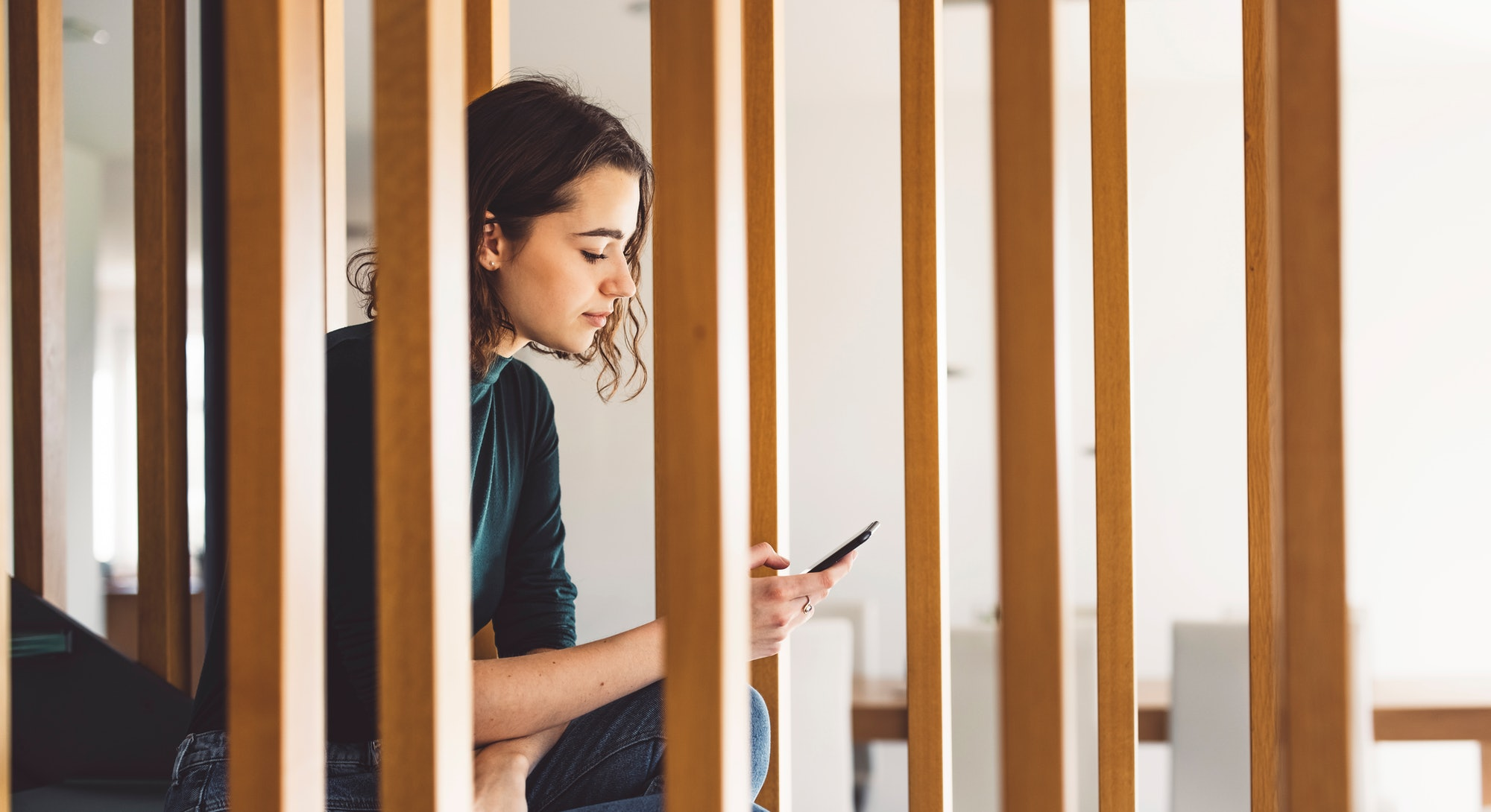 A woman sits on a staircase with her phone. Being constantly online creates a state of online vigila...