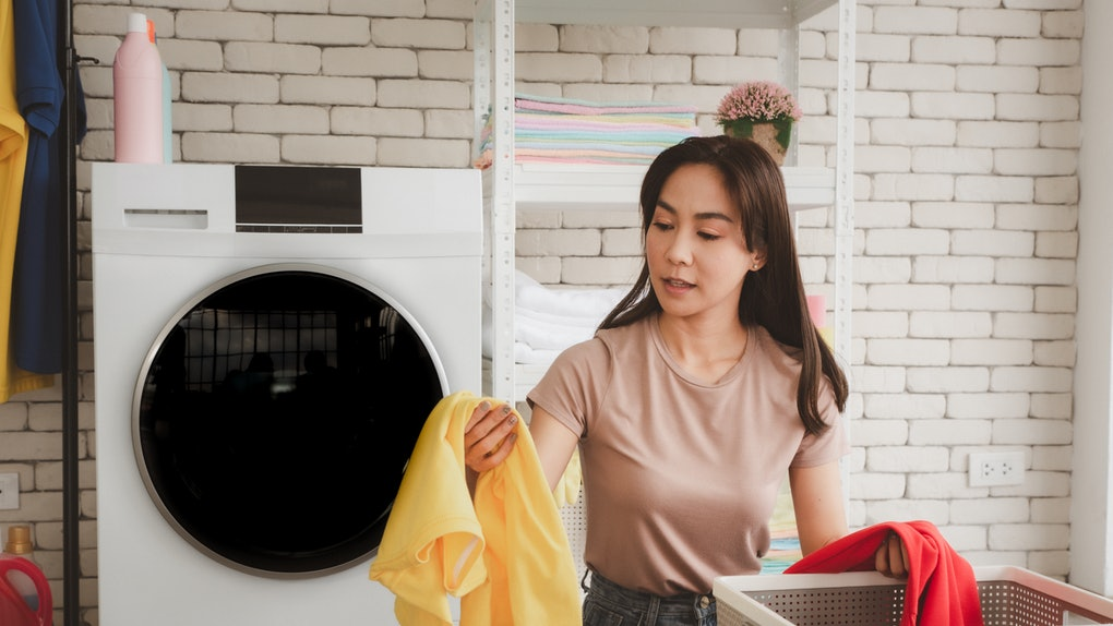 A woman sorts laundry in a bright laundry room.