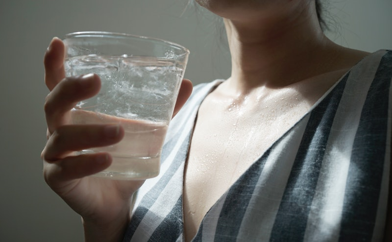 A woman drinks a glass of water. Here's what to expect from Dry January