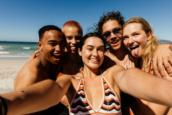 A group of friends takes a selfie on the beach while on vacation before quarantine.