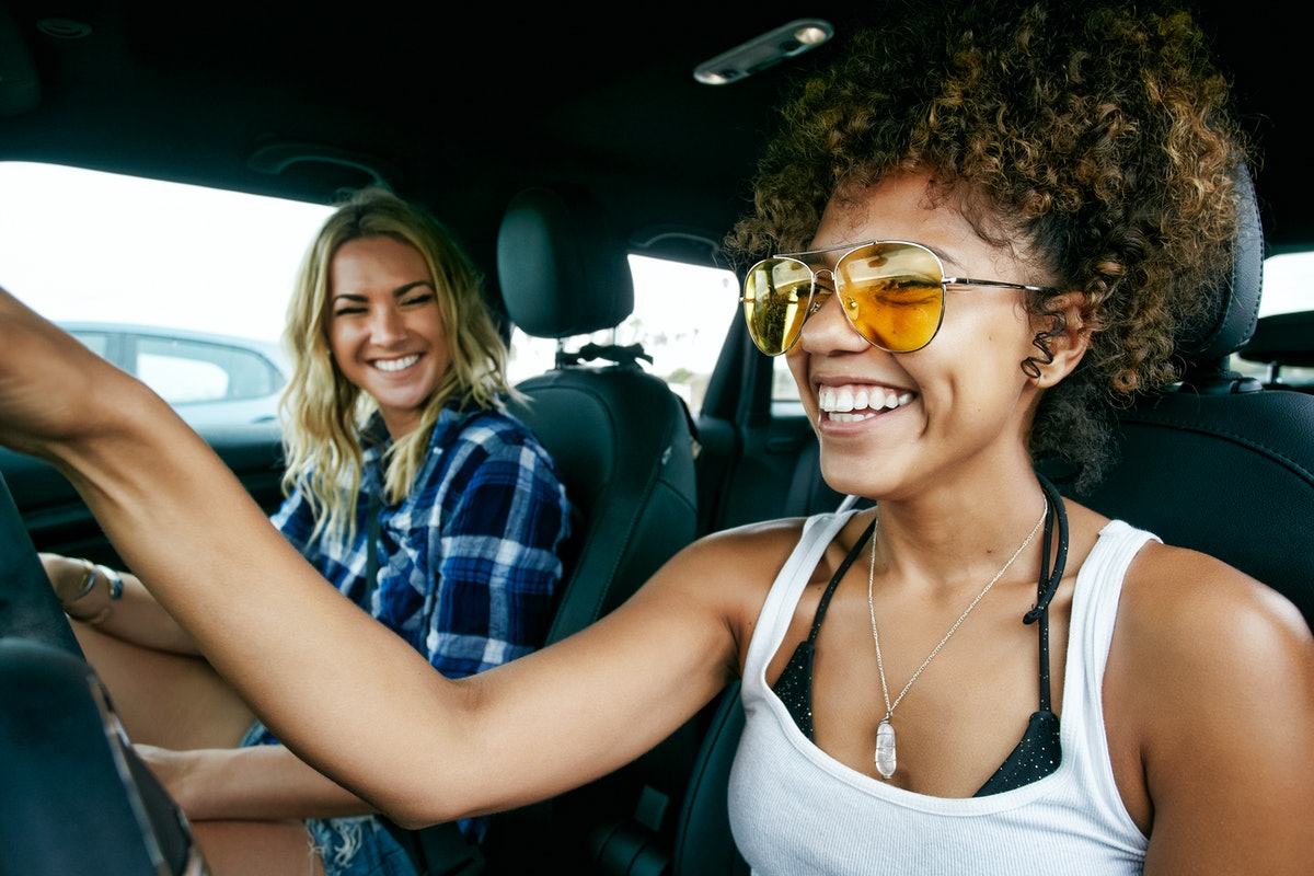 Two friends take a road trip together before quarantine, and laugh in the car.