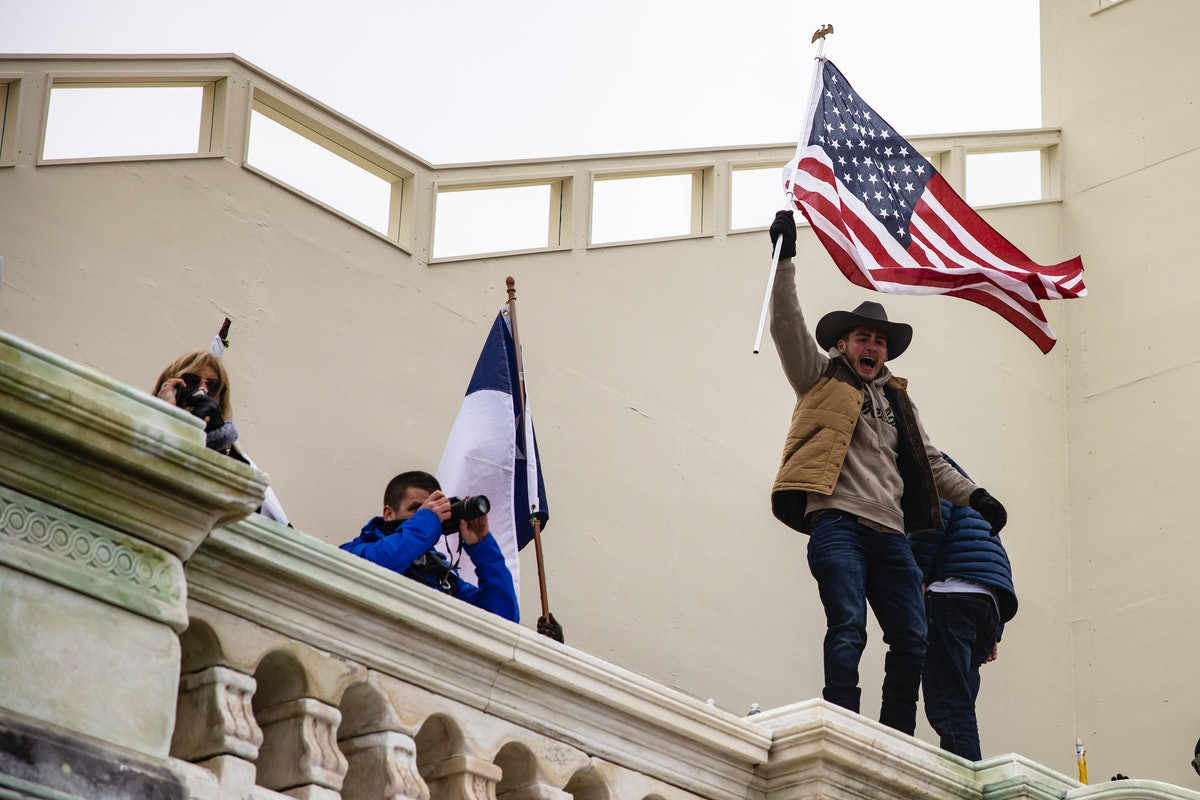 A man in a cowboy hat waves an american flag on the walls of the Capitol. Photos of Wednesday Jan 6 Capitol Building insurrection