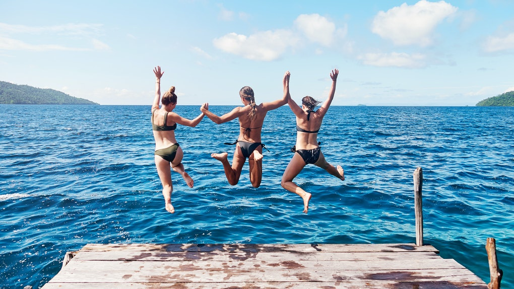 Three friends jump into a blue lake off a dock in the summer.