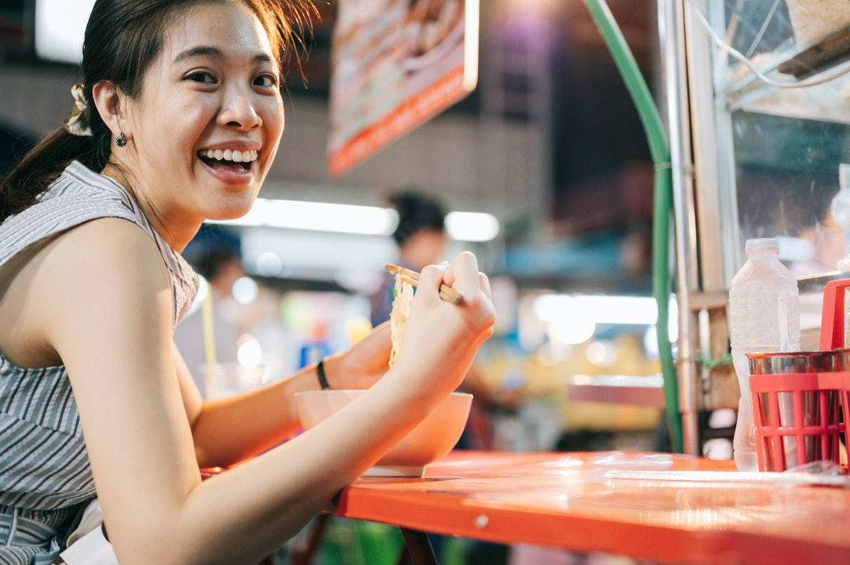 A happy woman eats noodles from a vendor while on vacation.