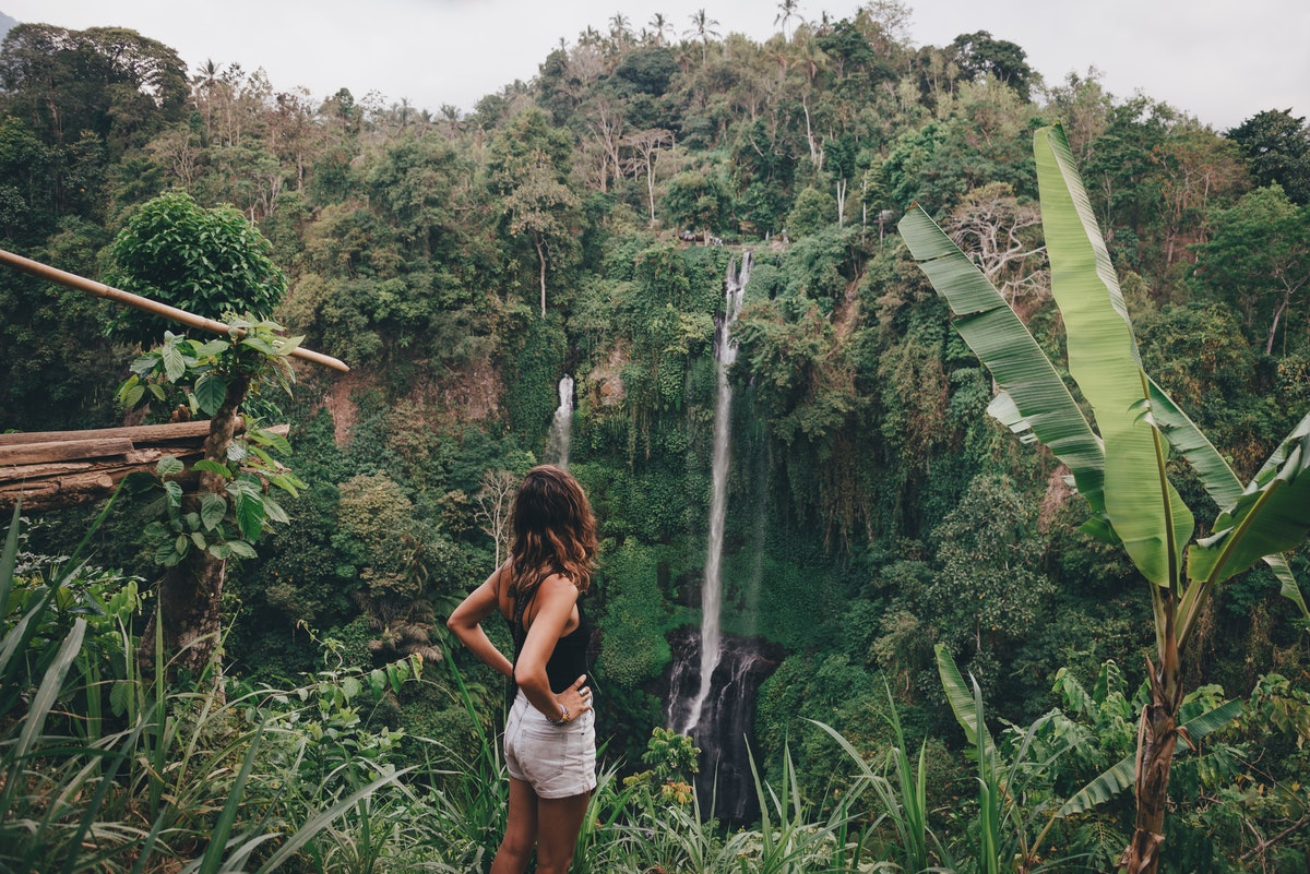 A young woman stands in front of a waterfall while on a jungle vacation before quarantine.