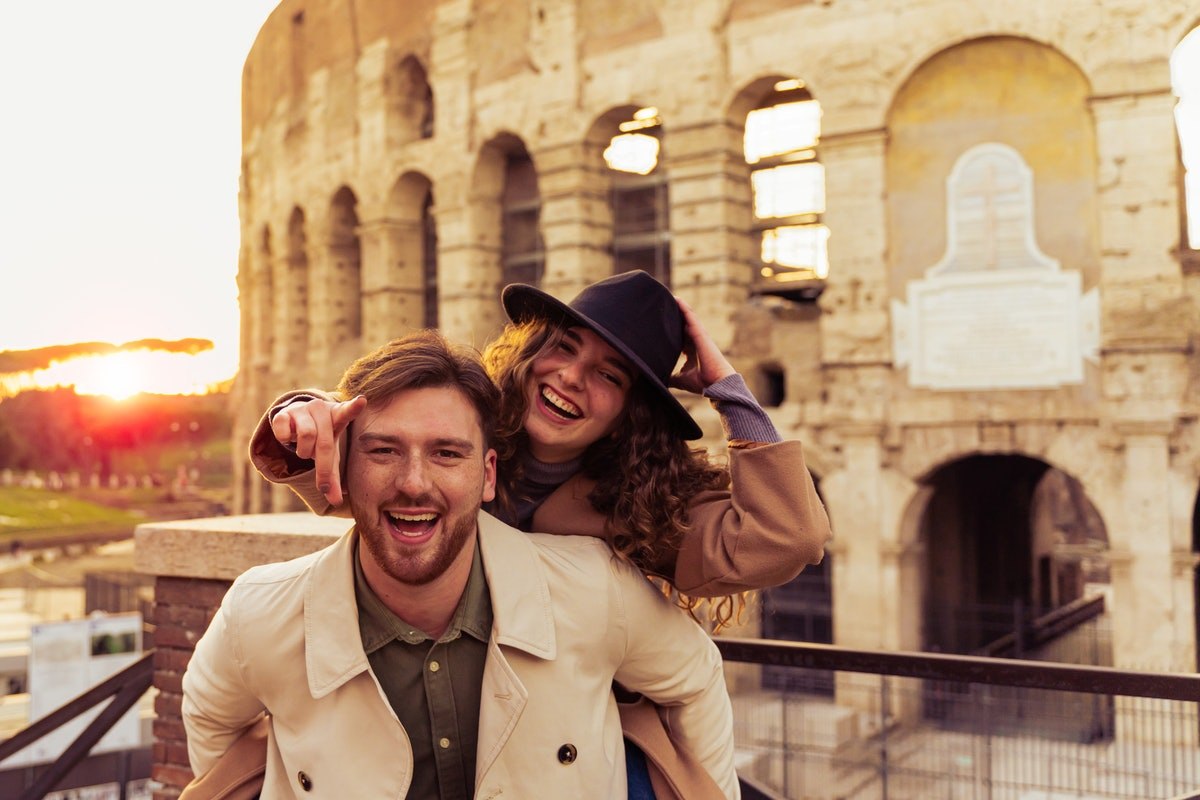 A couple poses by the Colosseum in Italy on vacation.
