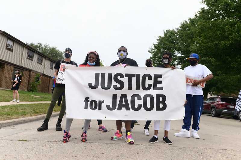 """Protestors hold up a sign saying """"Justice for Jacob,"""" a reference to Jacob Blake. Here's how to help..."""