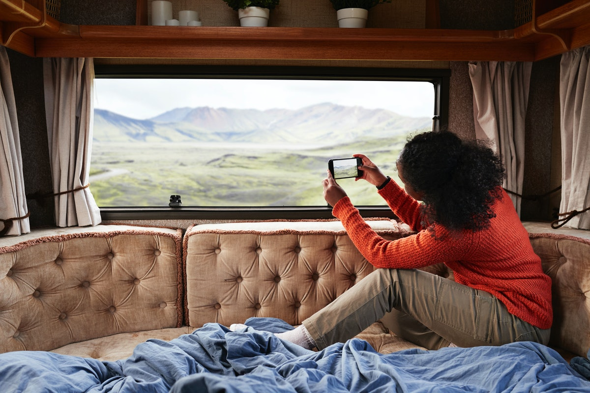A woman takes a picture of the landscape while sitting in the back of a RV on vacation.