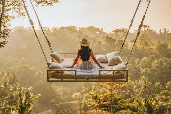 A young woman sits on a bed over the jungle in Bali, which some might consider a dream vacation on TikTok.
