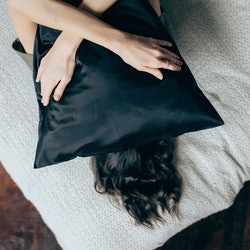 A woman lies down on a bed with a black pillow over her face. Experts share ways to cope when the news is traumatizing.
