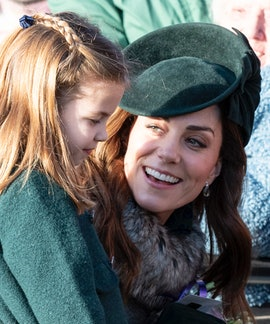 Kate Middleton wears a forest green hat and coat as she crouches down to speak with Princess Charlotte, who wears a matching coat.