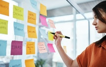 A person writes on multi-colored Post-its that are stuck to a glass wall. Making vision boards is great, but it's not the only goal-setting exercise out there.
