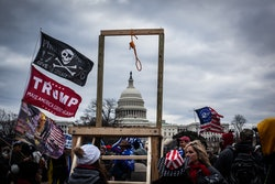 A scaffold and noose stands with the Capitol in the distance. A crowd holds various flags in support of President Trump.