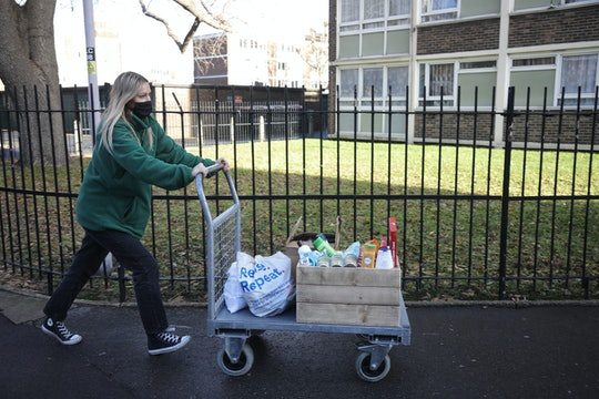 woman pushing cart home from food bank