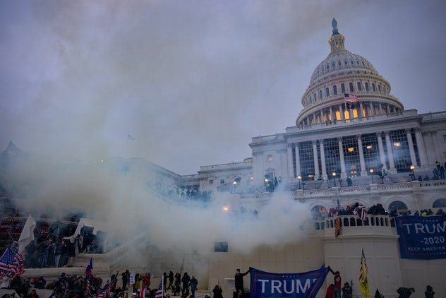 The Capitol with crowds holding Trump flags and tear gas visible in the air.