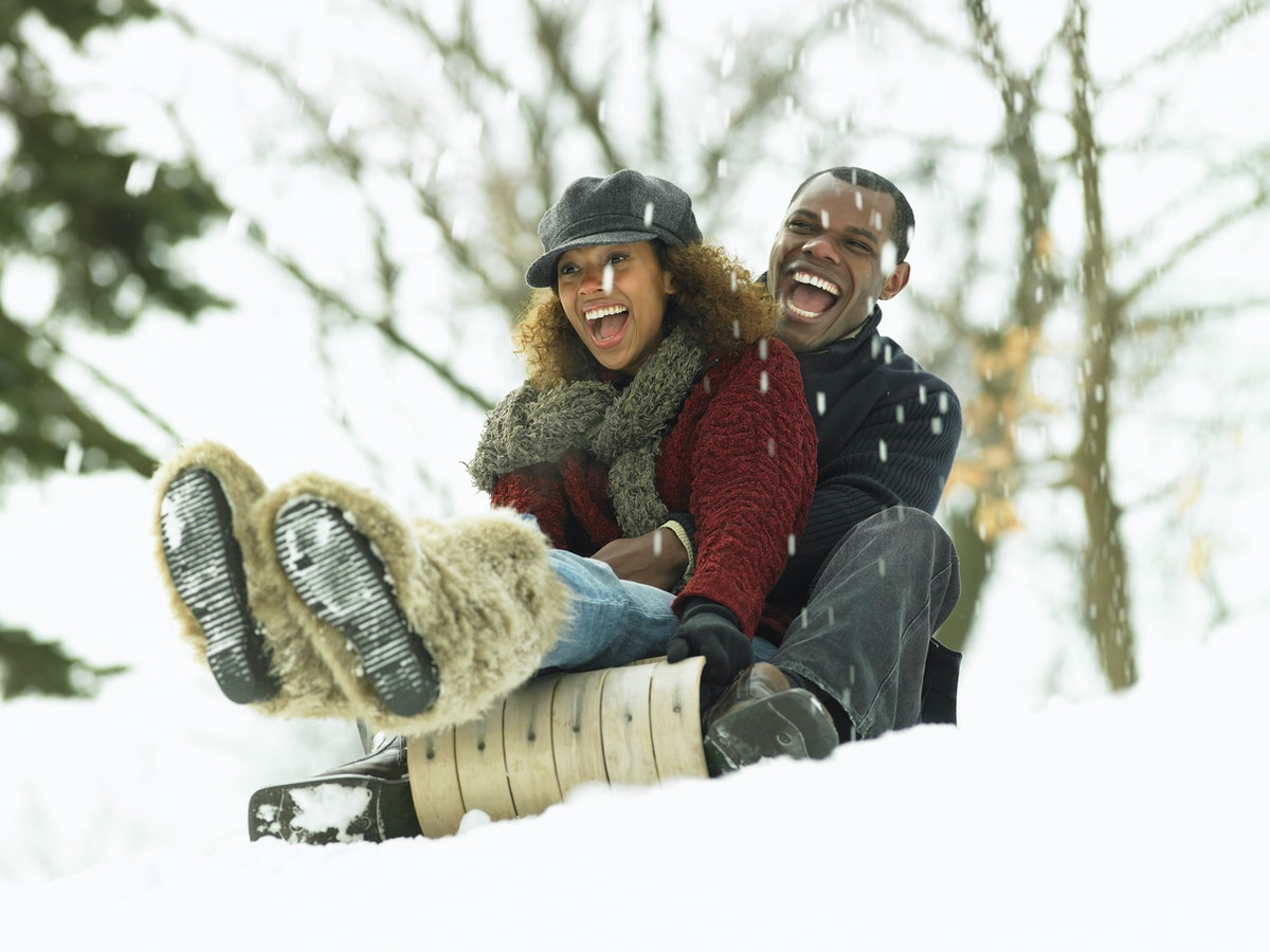 A young couple goes sledding in their backyard on winter day.