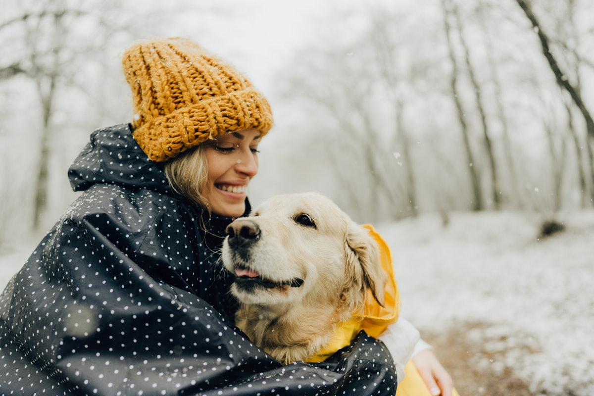 A young woman snuggles with her dog while playing in the snow.