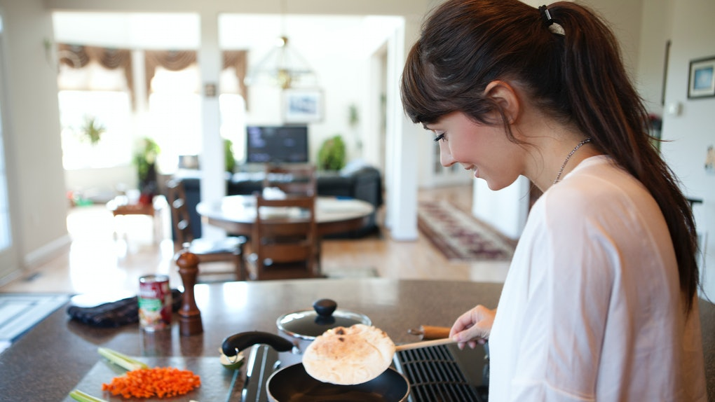 A happy woman flips a tortilla in a pan in her bright kitchen before filling it with veggies.