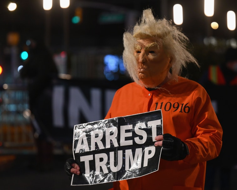 """A man in a Trump mask holding a sign that says """"arrest Trump."""""""