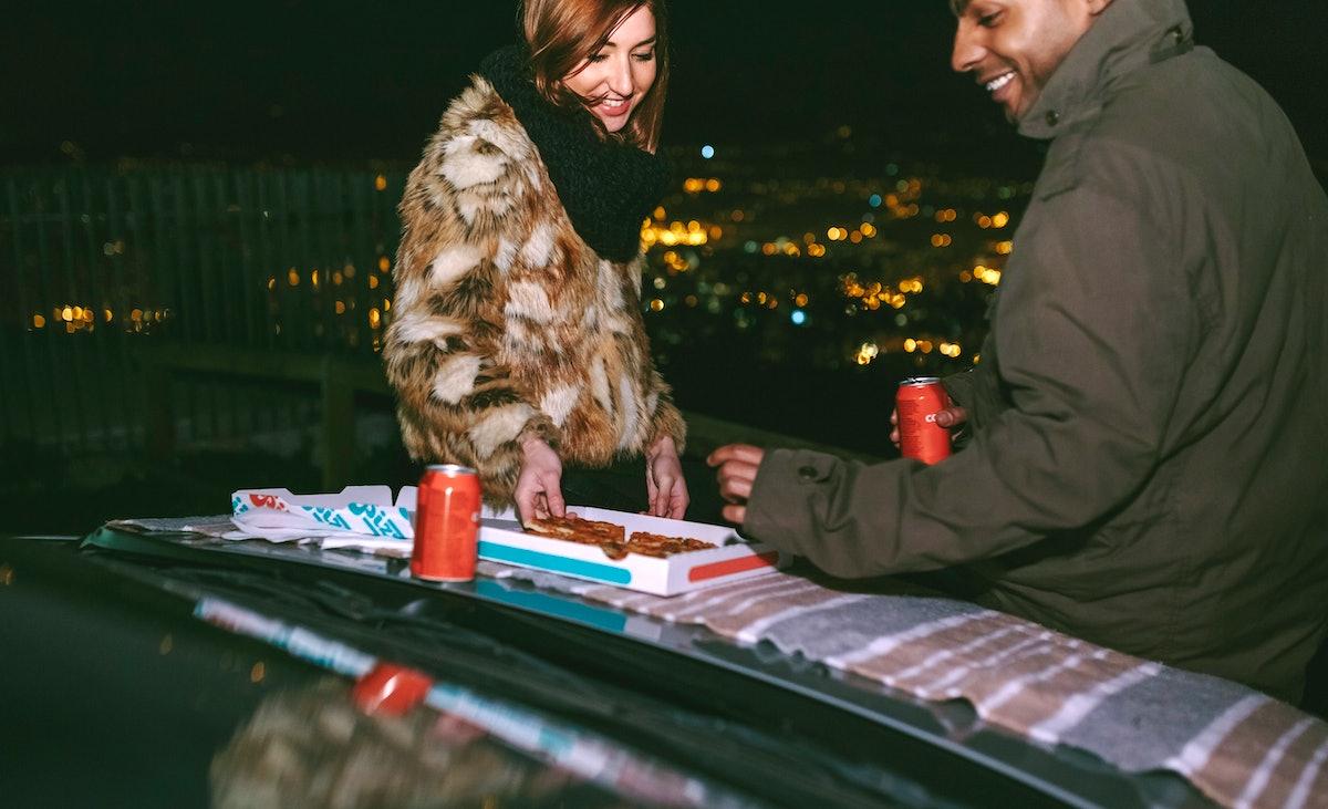 A happy couple enjoys a pizza on top of a car.
