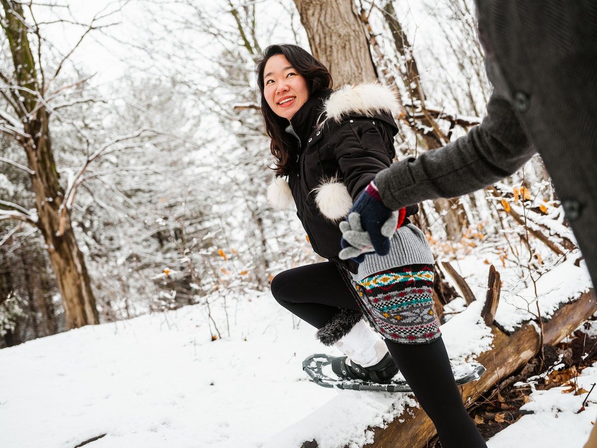 A young couple goes snowshoeing in their backyard on a winter day.